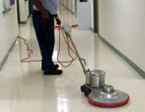 Worker buffing a hallway floor